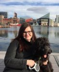 Dr Jana Funke sitting beside a harbour with a large black dog in her lap.