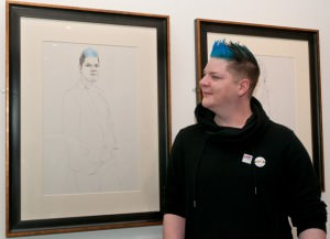 Young man with quiff of bright blue hair looks at a pencil portrait of himself