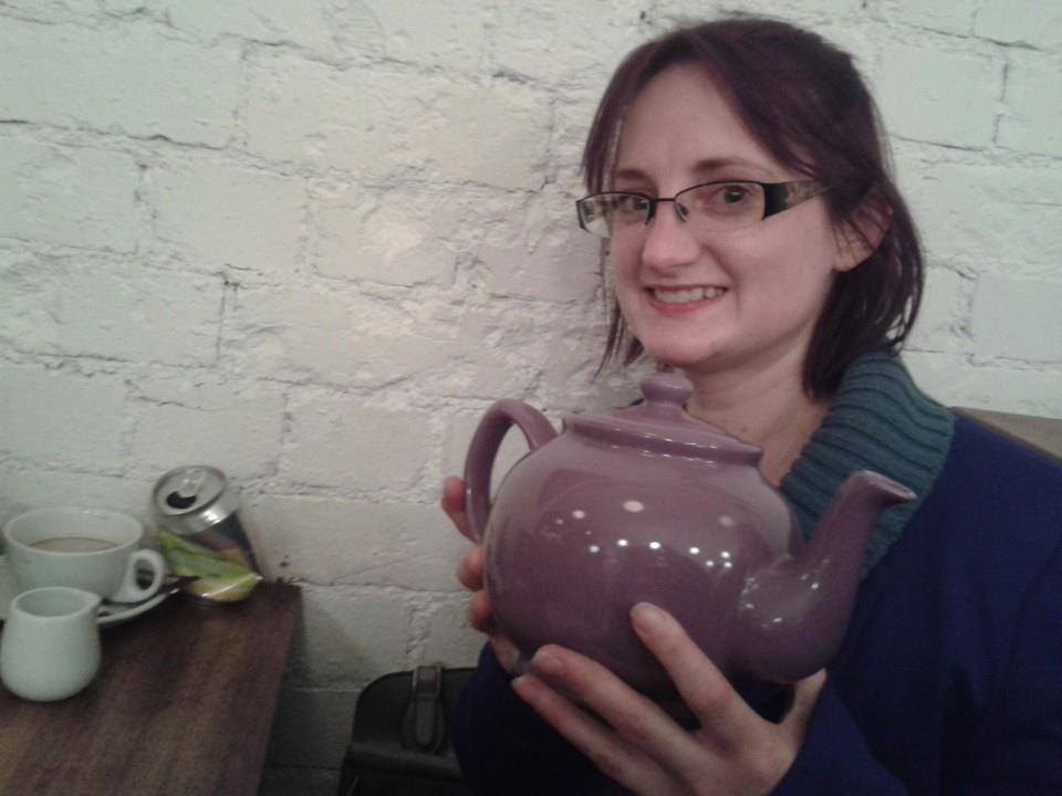Smiling young woman holding a large purple ceramic teapot.
