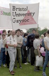 Three young men in a large crowd holding a white banner that has a pink triangle and text Bristol University Gaysoc in black letters
