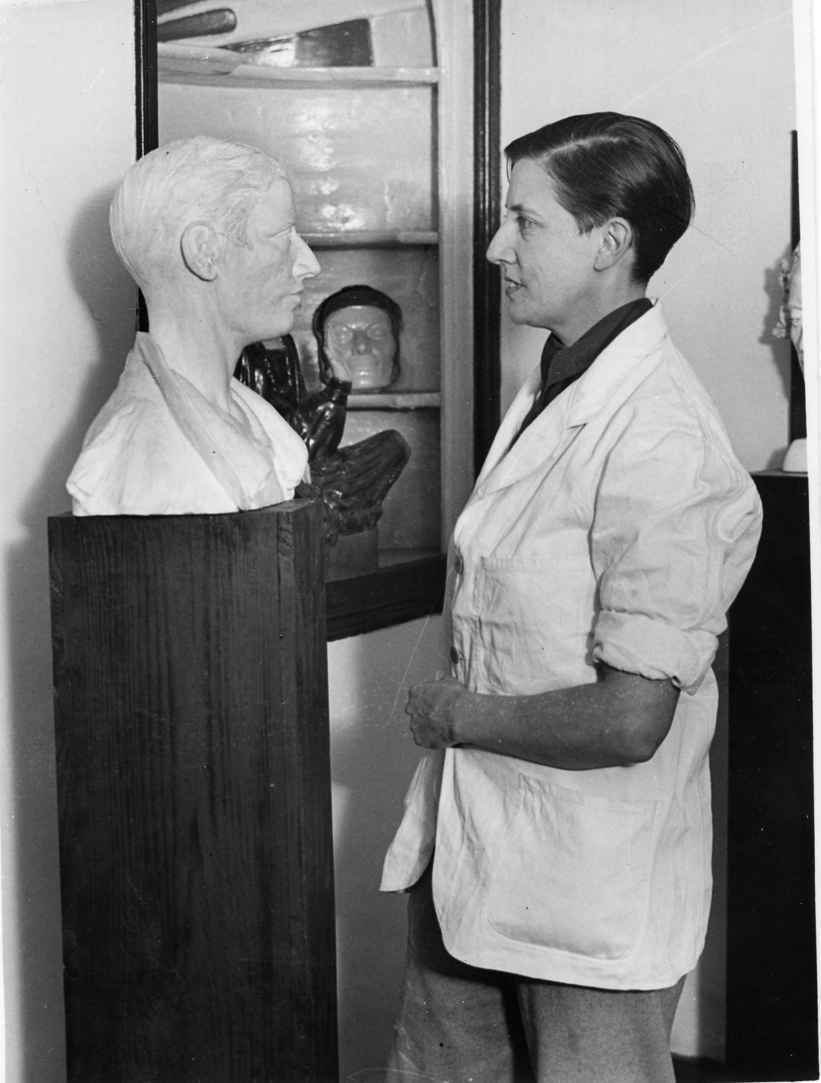 Standing young woman wearing overalls and short hair, facing a sculpture bust of herself.