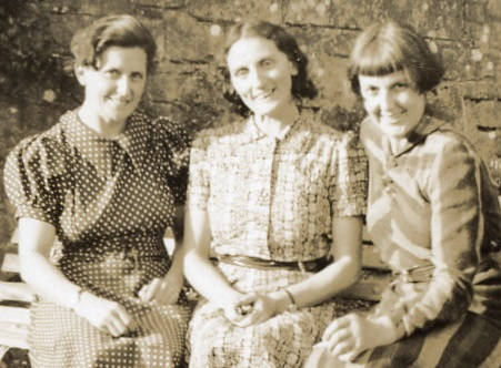 Three smiling women sitting on a bench in a sunny garden