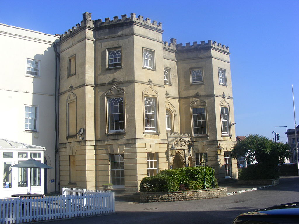 An imposing 3-storey stone building with castellations at roof level making it look slightly castle-like.