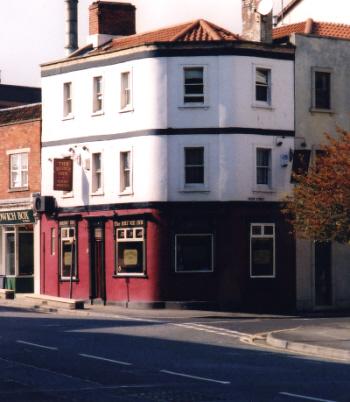 Outside of Bridge Inn. 3-storey Victorian building on corner, tiled roof. Ground floor painted deep red; white above.
