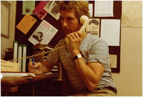 A male volunteer at the Bristol gay switchboard is answering a telephone call.
