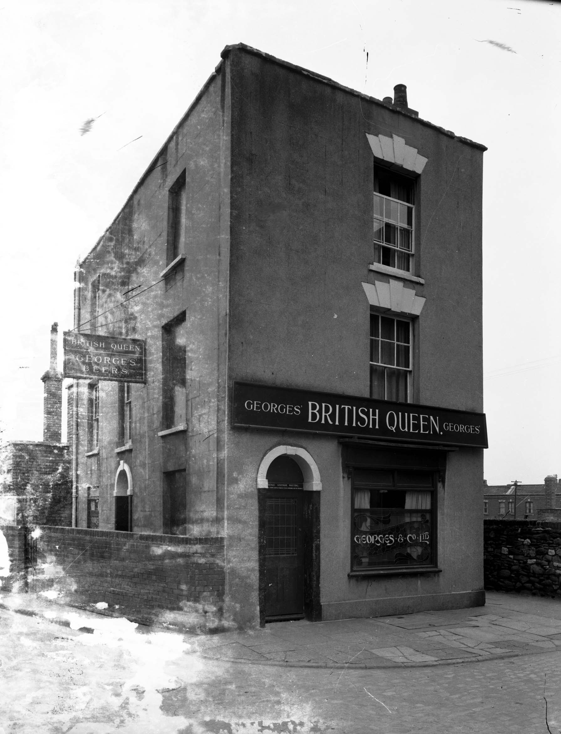 Small 3-storey Victorian detached building on a deserted street corner. Sign says British Queen - Georges Beers