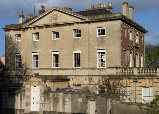 Large 3-storey stone-faced Palladian house, 1st and 2nd floors each having five sash windows and an imposing pediment above.