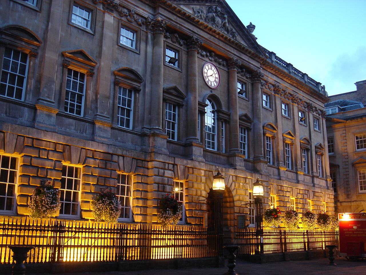 Grand 3-storey Georgian stone building at dusk. Colonnaded front topped by a pediment.