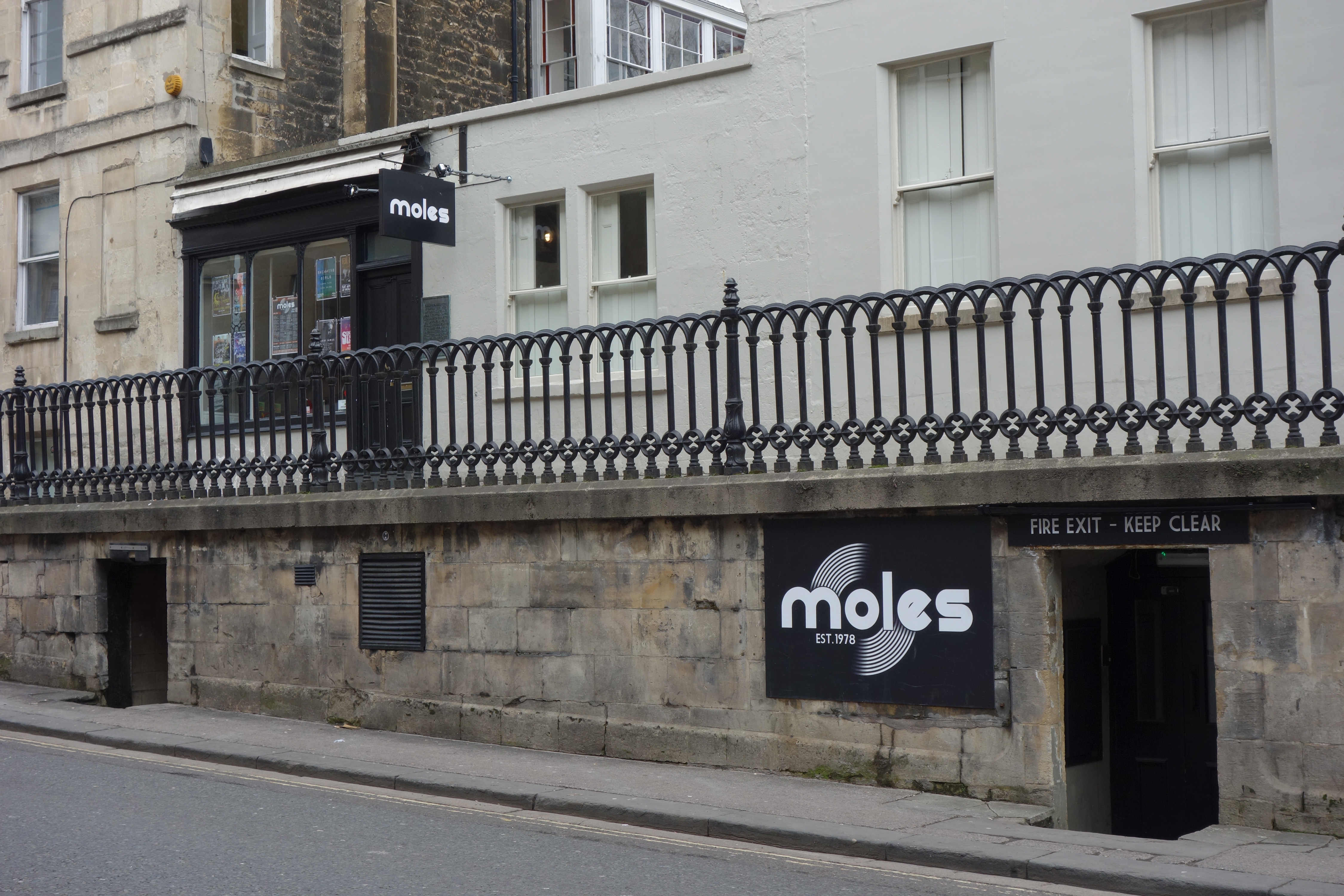 A small door in a low stone parapet with a sign Moles, with a shop front above also signed Moles