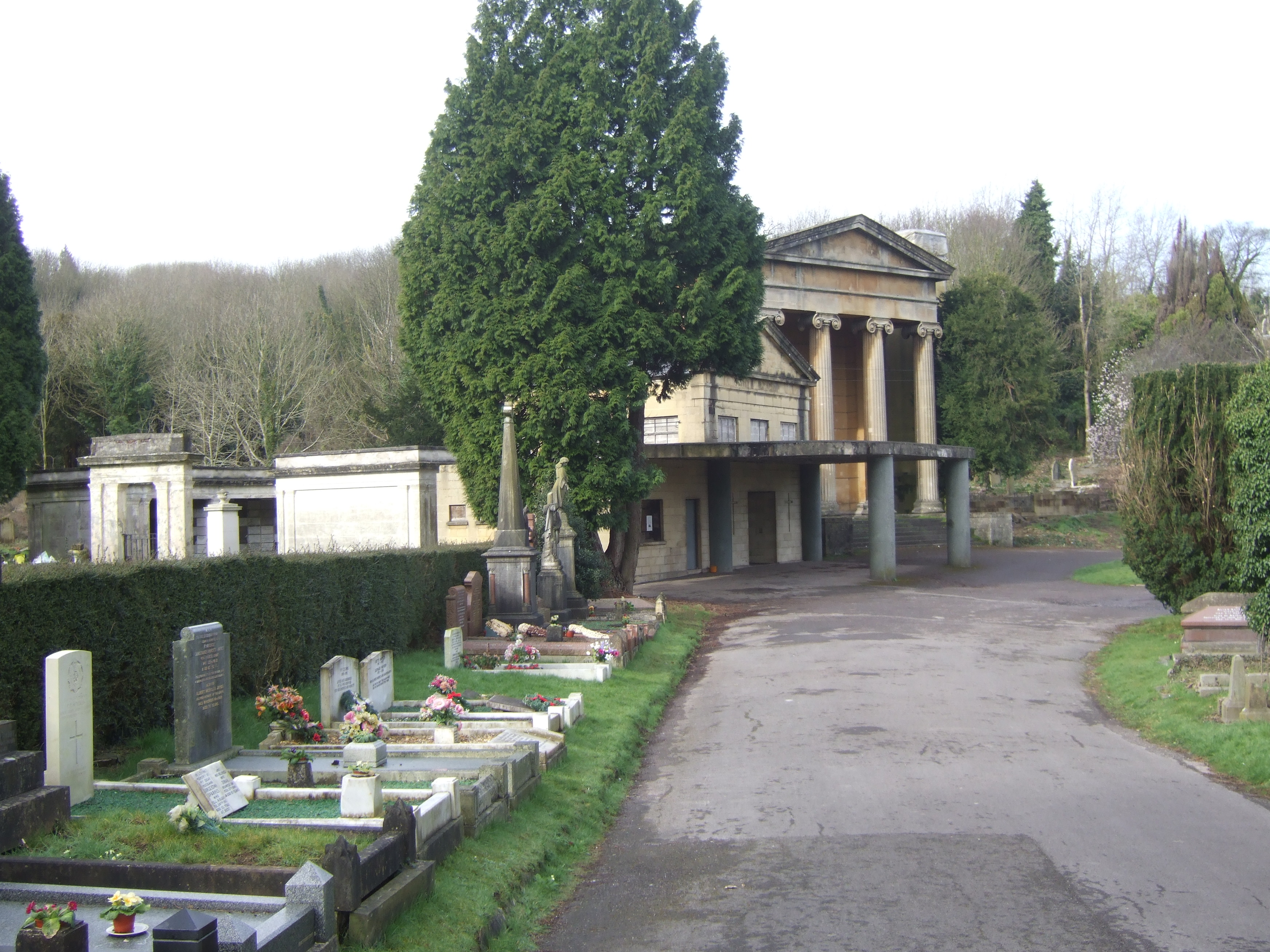 Crematorium chapel with classical columns surrounded by graves and large trees.