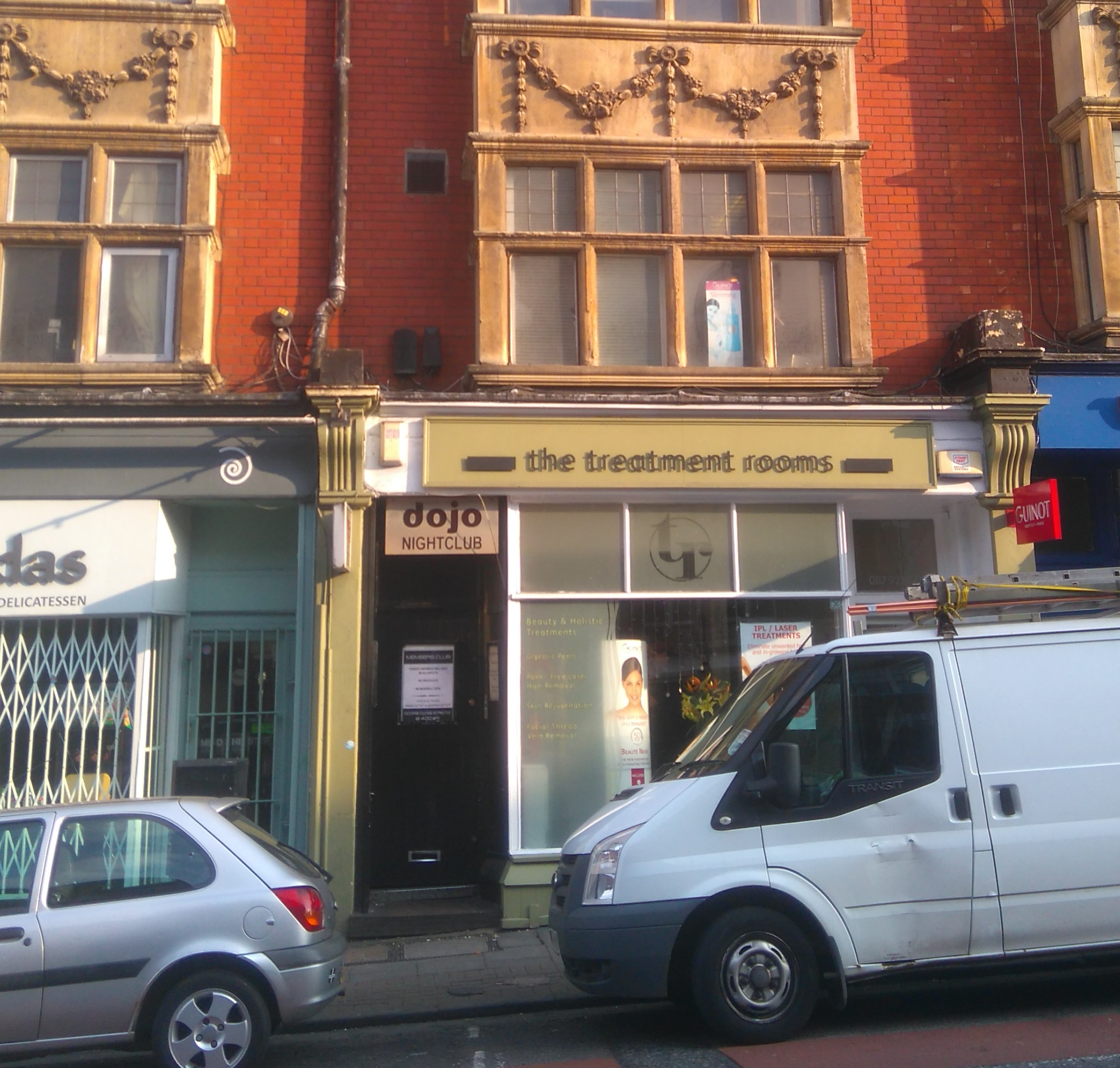 Shopfronts with parked cars and a black door signed Dojo Lounge