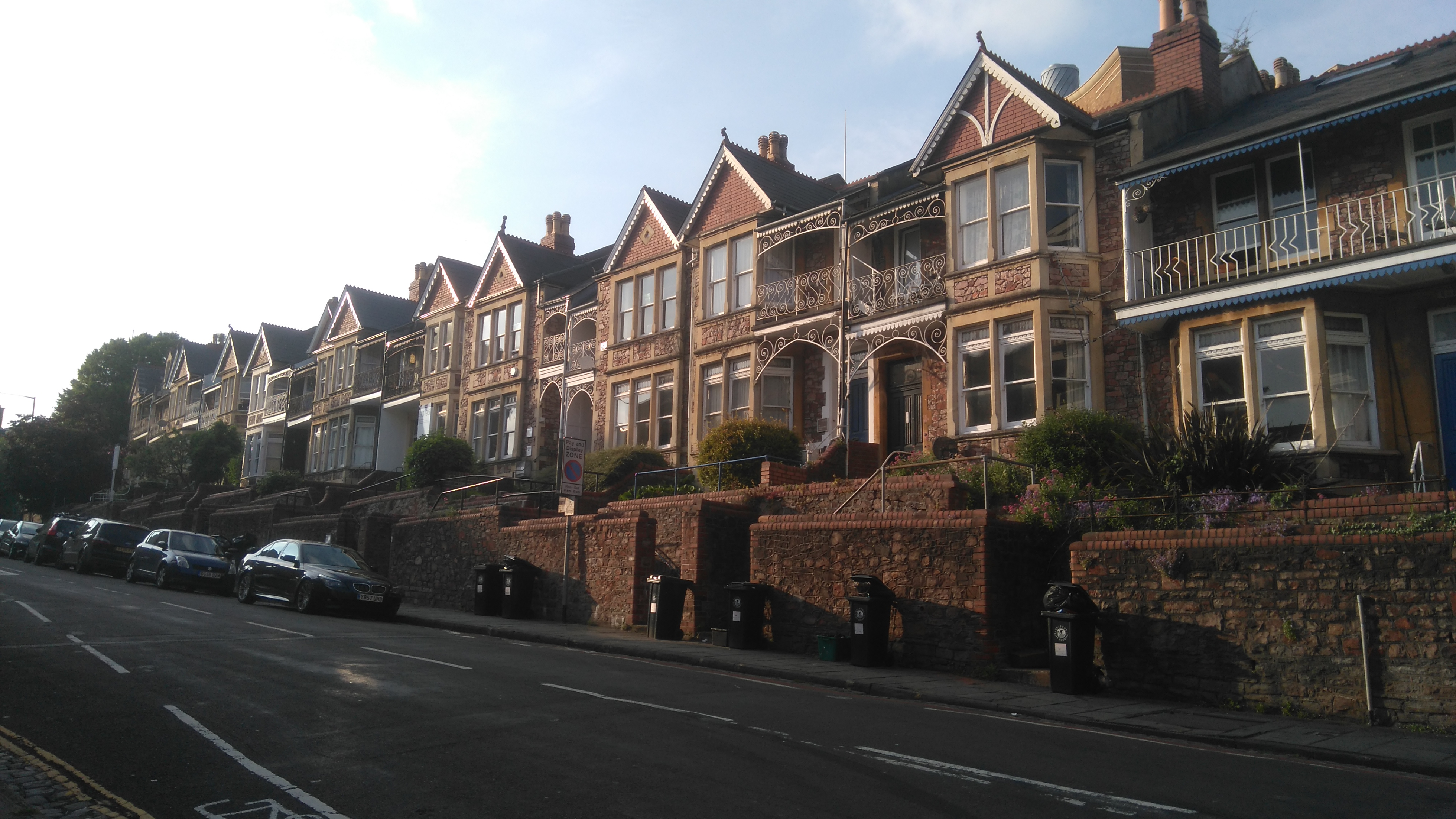 A sloping street with big Victorian stone houses and high garden walls on a sunny evening