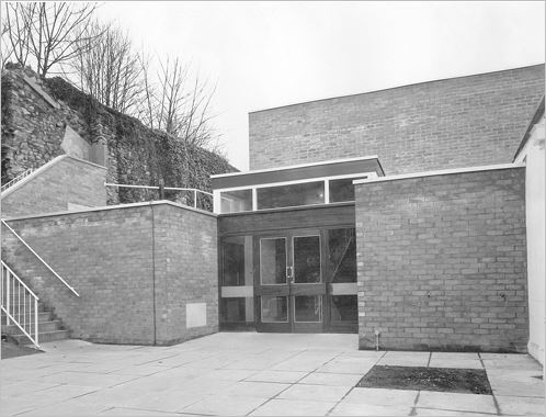 A 1960s brick building with a glazed entrance door but no windows, and a barren paved courtyard in front.