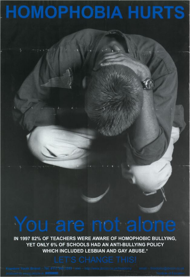 Young man seen from above, dejectedly crouching with head in hands. Text says homophobia hurts, you are not alone.