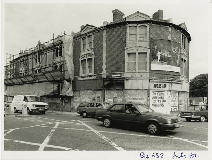 Derelict 3-storey Victorian building on a corner, ground floor and windows boarded up. Cars passing in foreground.