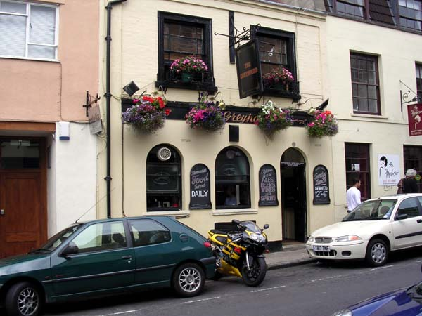 Front of small 2-storey Victorian pub, bright yellow wall, black door and windows, and six hanging baskets overflowing with blooms.