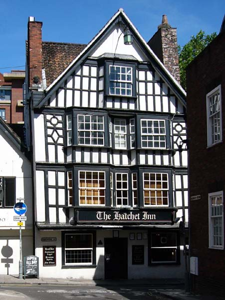 A 4-storey white-walled black timber framed house built in 1606, on a blue-sky summers day.
