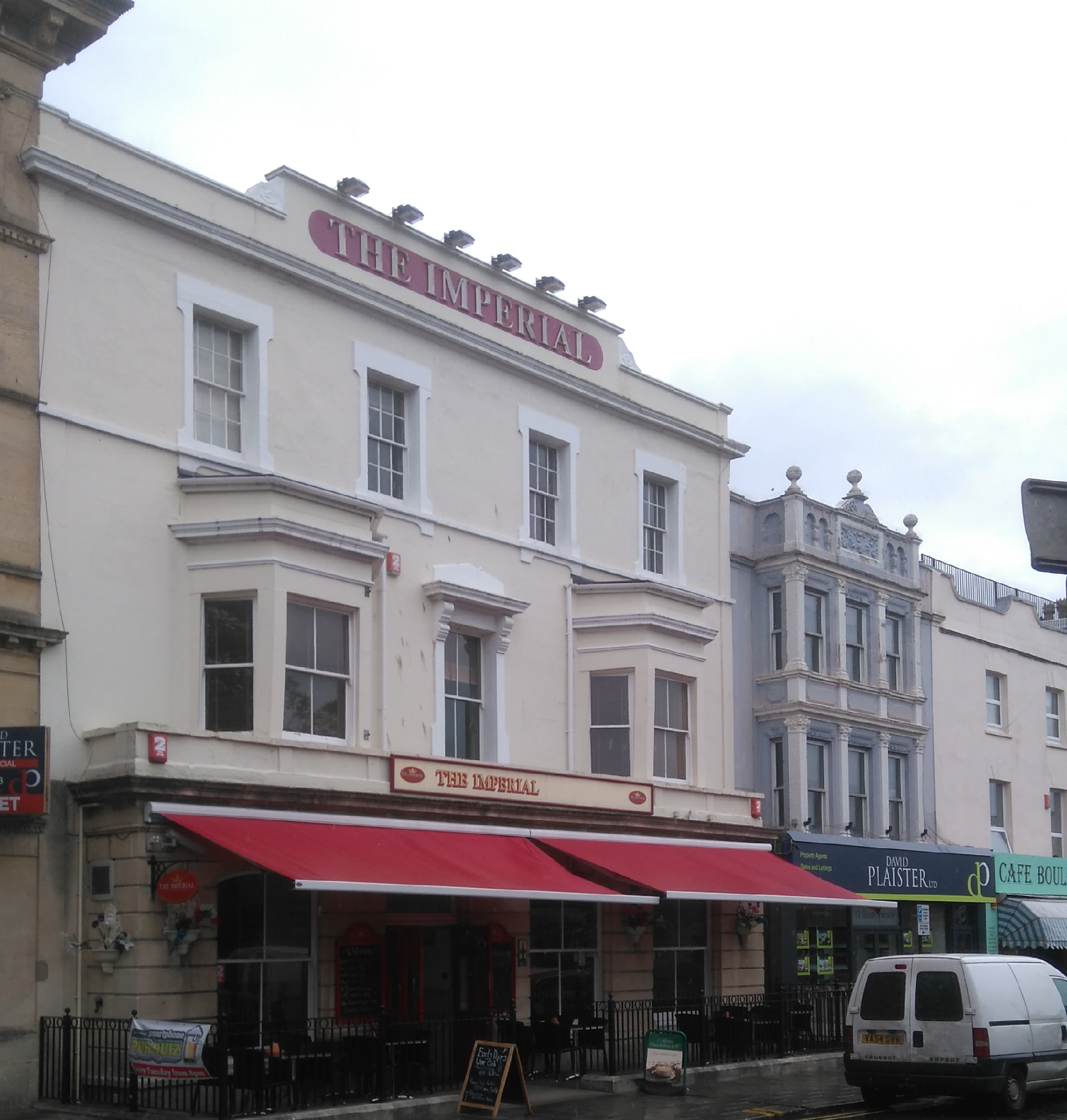 A three-storey white Victorian hotel with railings and red sun blinds. The words The Imperial are displayed at the roofline.