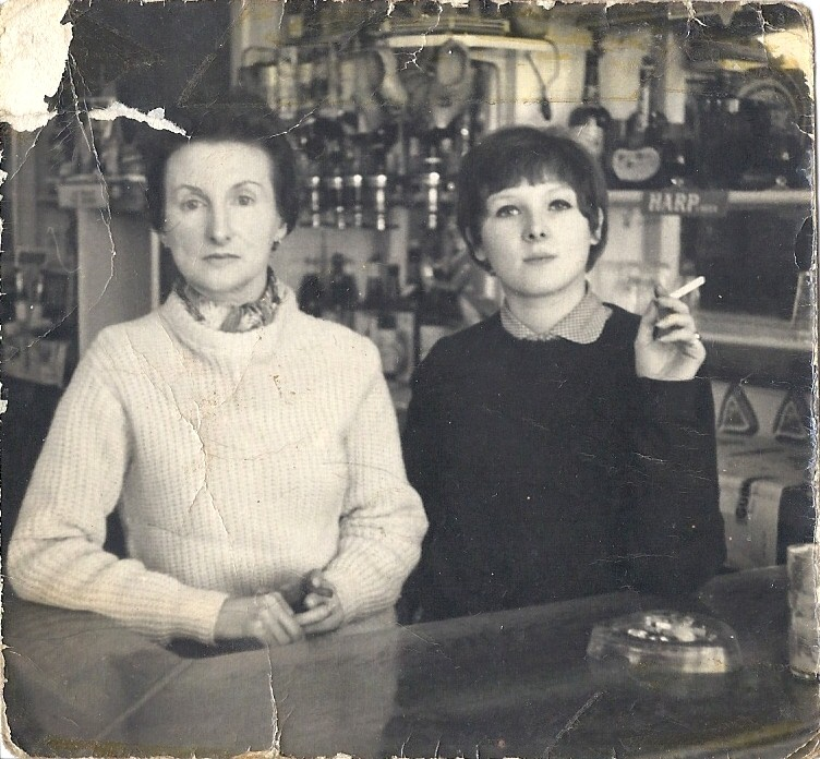 Middle-aged Joan and younger Anna standing behind bar with optics behind. Both wearing knitted pullovers, Anna smoking a cigarette.