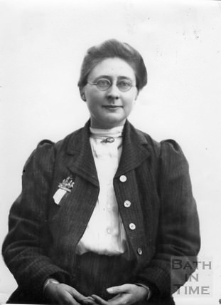 Black and white portrait photograph. Blathwayt looks straight into the camera, she wears glasses and large double breasted coat. Hands rest in her lap. Expression is between a smile and determination.