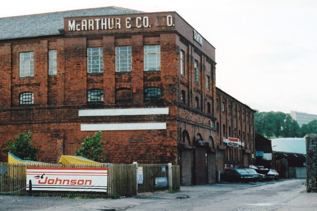 Large Victorian 4-storey red brick industrial warehouse on a deserted lane with metal windows and shuttered doors. Looking rundown.