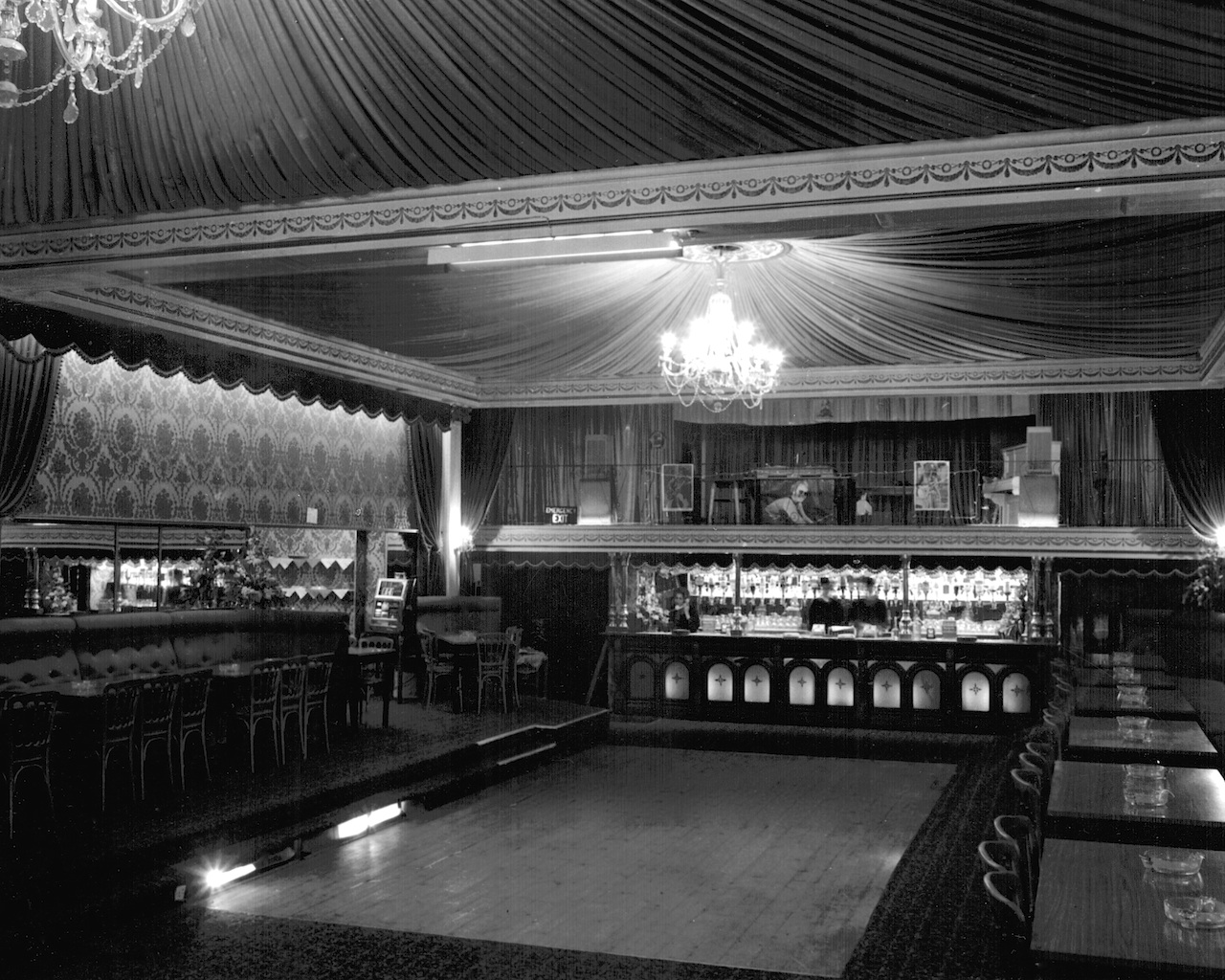 Large rectangular dance floor with camp swish fabric drapes and ornate chandelier overhead, long bar with altar-like frontage behind.