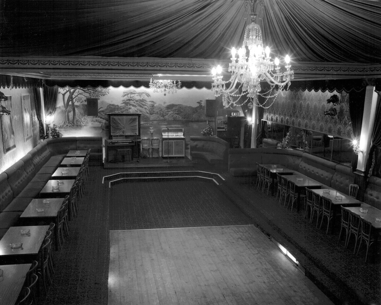 Large rectangular dance floor with camp swish fabric drapes and ornate chandelier above, tables and single long bench seat down each side.