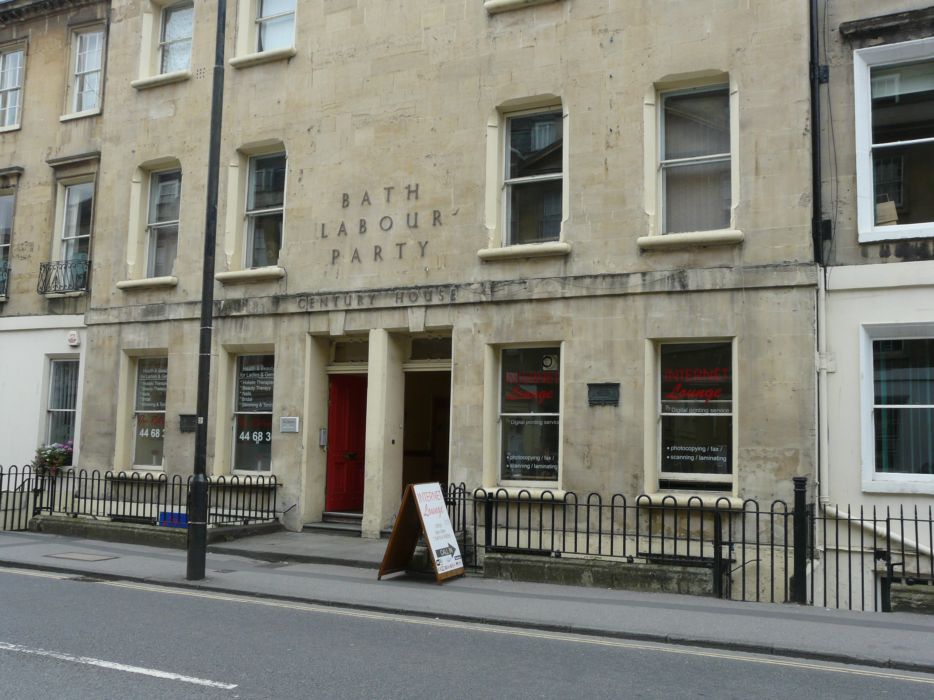 A stone building with a sign saying Bath Labour Party and railings in front of the basement