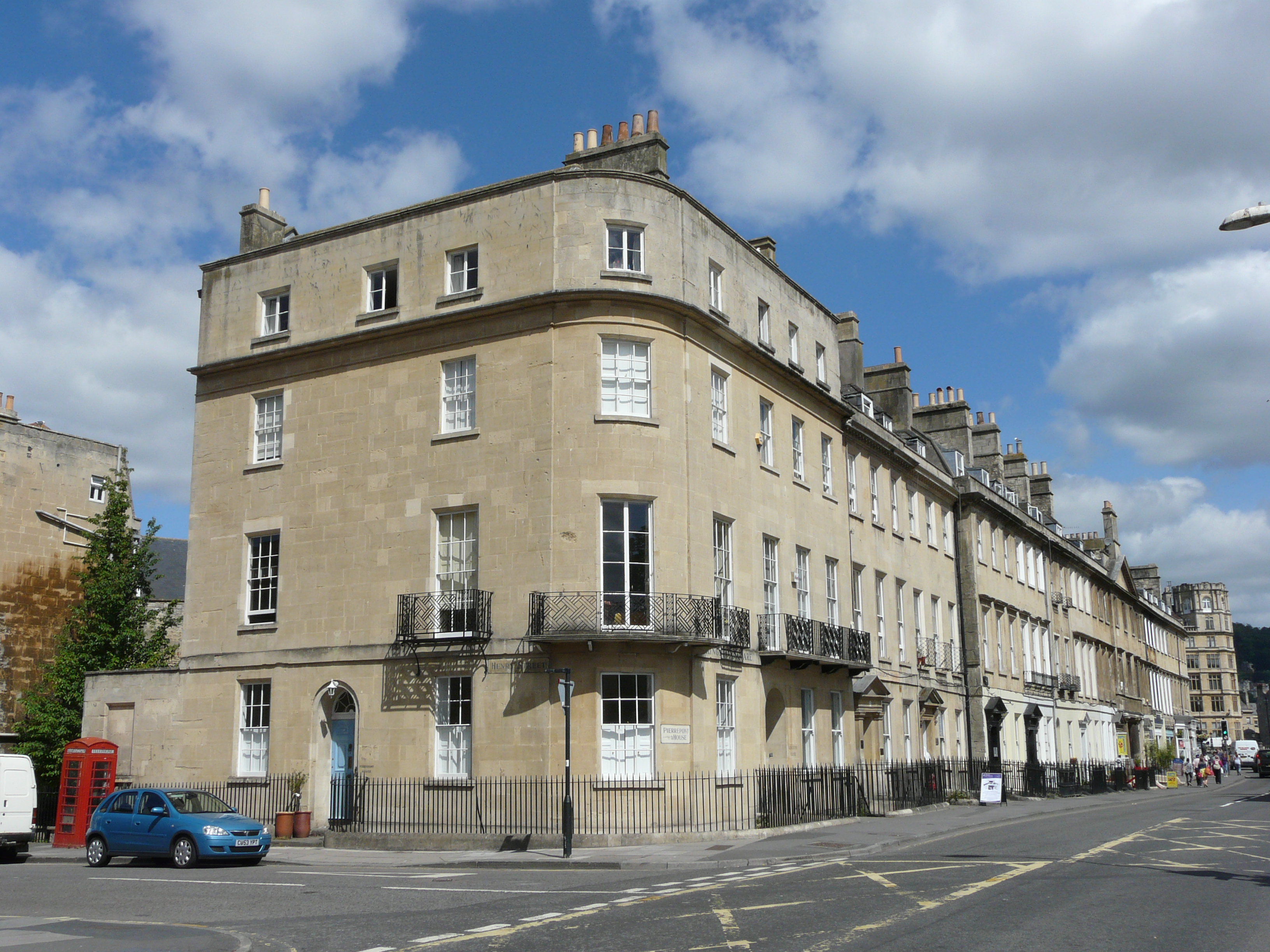 A four-storey stone building on the end of a row of houses on a sunny day