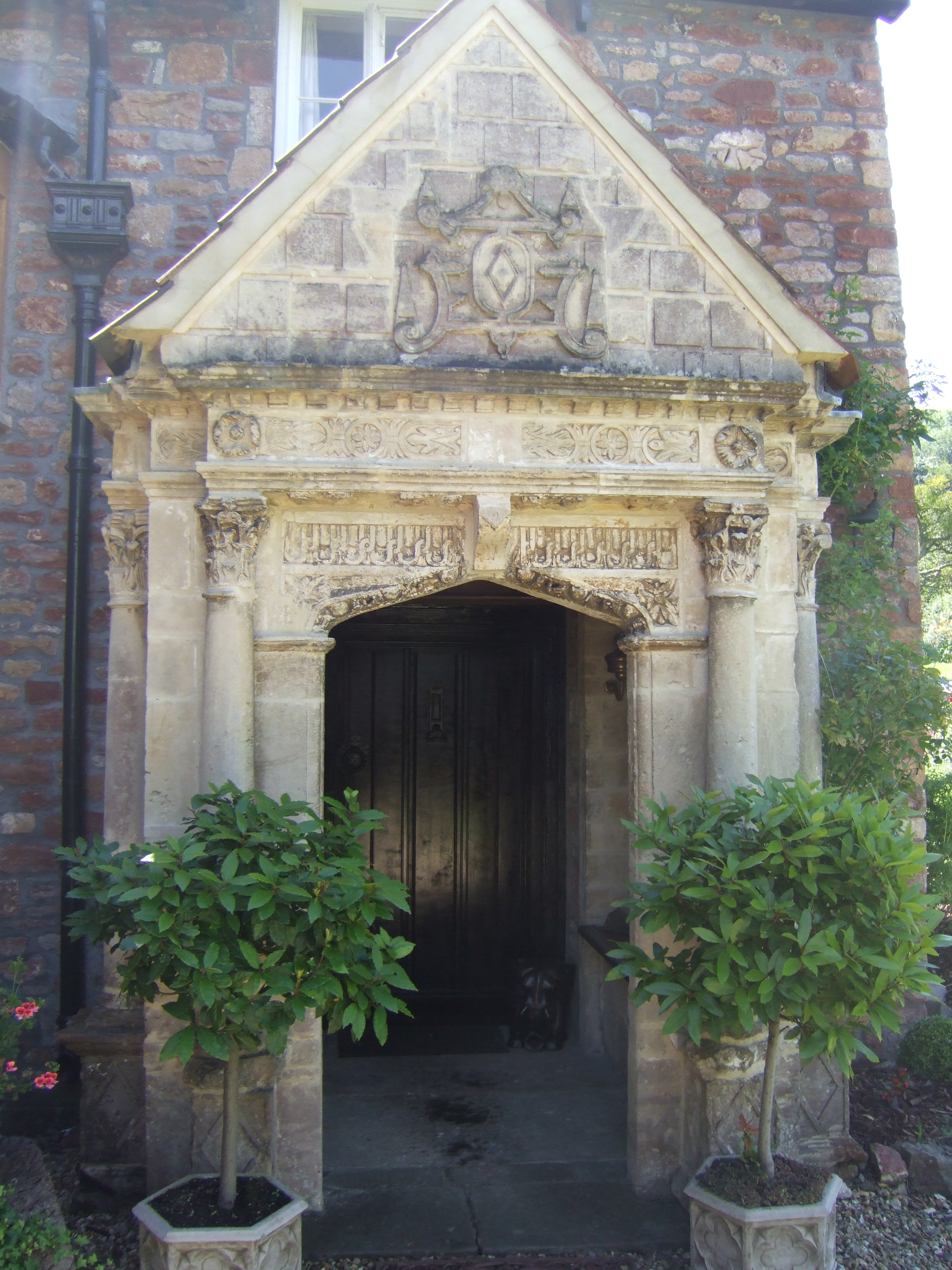 A 17th century stone porch with ornate carving and columns, with trees in pots