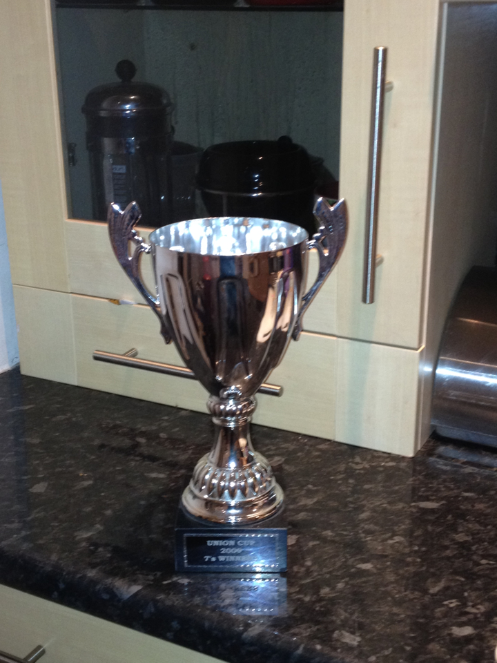 A silver sports trophy in the form a cup with handles on a square black plinth