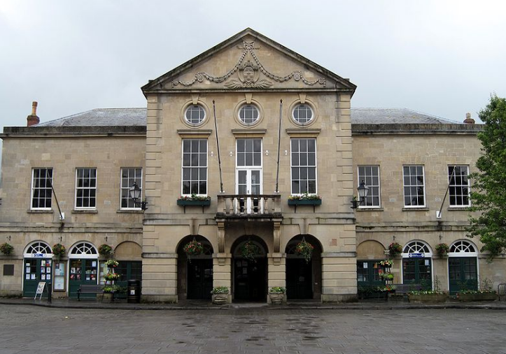 A big stone Georgian building with pediment and balcony facing a paved square.