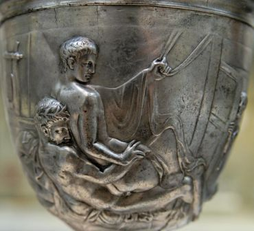 Embossed Roman cup showing two naked men, the young man being anally penetrated by the older.