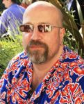 Middle-aged man with beard and moustache and wearing bright floral shirt and sunglasses