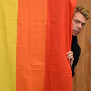 Young man peeping from behind a rainbow-coloured curtain