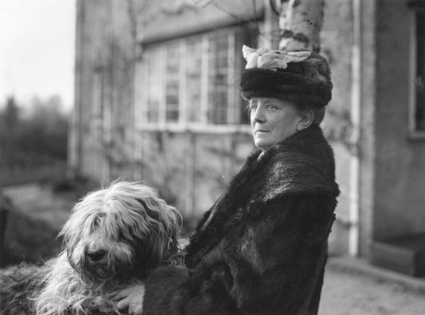 Elderly lady wearing fur coat and hat with a large dog, standing outside a house
