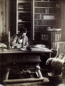 Middle-aged man with facial hair and wearing tweed jacket and fur hat sitting at an ornate desk with book-lined shelves behind.