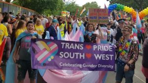 Group of happy brightly-clothed young people on a Pride Parade with a 'Trans Pride' banner