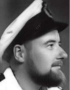 Side of man's face, perhaps in his mid 30s with beard and moustache and wearing a seaman's cap and shirt.