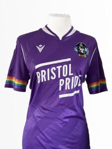 "Bright purple football shirt with rainbow stripes on sleeves and logo ""Bristol Pride"""