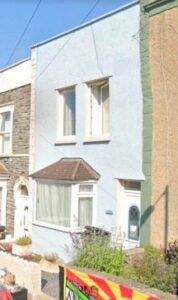 Front of small terraced house, bay window and door and two small windows on first floor.