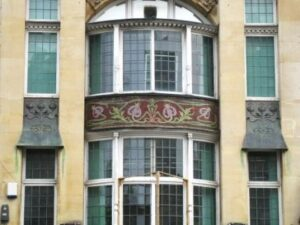 Ornate burgundy and gold mosaic between and first and second floor bow windows