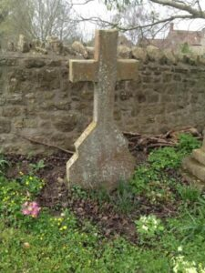 A plain stone cross in front of a stone wall.