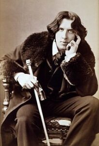 Oscar Wilde about 28 with long flowing hair, seated , left hand rested against side of face, right hand holding walking cane.