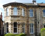 Large mid-Victorian 2-floor semi-detached house built of stone with imposing bay windows