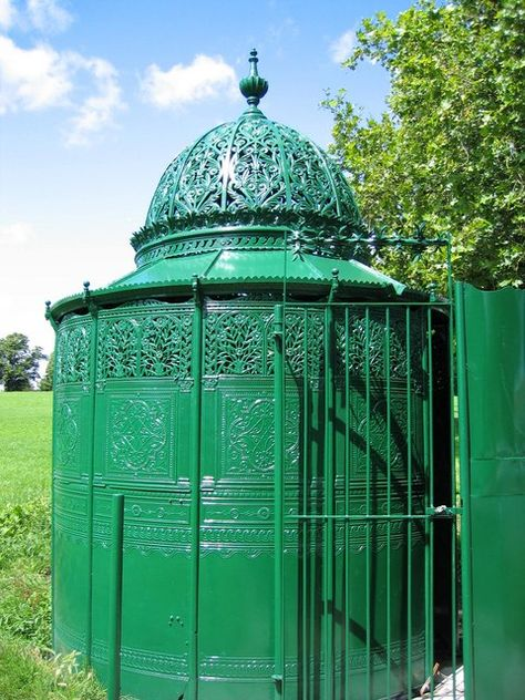 Ornate cylidrical cast iron enclosure, about 2m diameter, painted green
