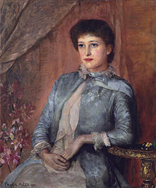 Oil painting of beautiful young woman wearing a blue frock-coat, seated with left arm resting on a table.