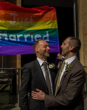 """Two happy smiling men under a rainbow banner with text """"just married"""""""
