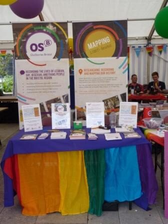 Table covered with a rainbow flag and leaflets