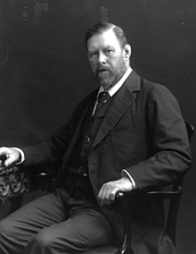 A middle-aged bearded man, wearing suit and tie, seated.